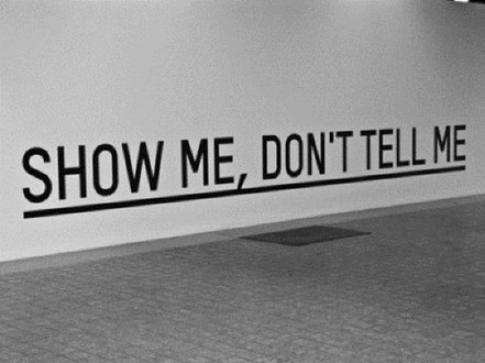 A photo of a wall with the words, Show Me Don't Tell Me, written in large letters.