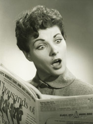 A photo of a woman reading a newspaper with a surprised look on her face. Her eyes are very wide and her mouth is open.